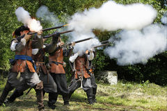 Musketeers in period dress firing rifles. Royalty Free Stock Images