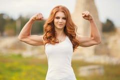 Muskler för visning för kvinnakroppbyggmästare Royaltyfri Bild