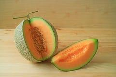 Muskmelon fresco maduro suculento da cor alaranjada Mouthwatering cortado do fruto inteiro imagem de stock royalty free