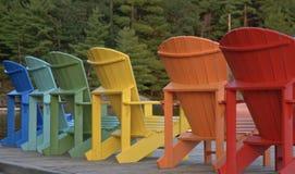 Muskoka Adirondack Chairs Multicolored. Rainbow of Muskoka Adirondack chairs in summer Royalty Free Stock Images