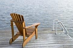 Muskoka Chair. One Muskoka chair on the dock by the lake Royalty Free Stock Photos