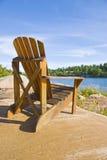 Muskoka Chair On a Big Rock. Single muskoka/adirondack chair sitting on a big and smooth rock by the lake Stock Photo