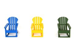 Muskoka Chairs. A row of colorful Muskoka chairs, isolated on white Royalty Free Stock Images