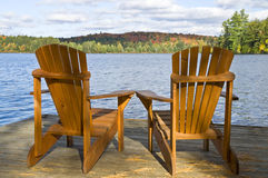 Muskoka Chairs. Two Muskoka chairs on the dock by the lake Stock Photos
