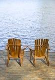 Muskoka Chairs. Two Muskoka chairs on the dock by the lake Stock Photo