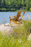 Muskoka Chairs On a Big Rock. Muskoka/adirondack chairs sitting on a big and smooth rock by the lake Royalty Free Stock Images