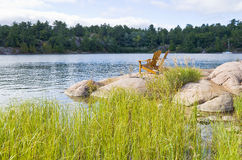 Muskoka Chairs On a Big Rock Stock Photo