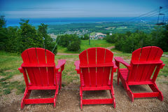 Muskoka chairs at Blue Mountain resort and village in Collingwoo. View of 3 red muskoka chairs at Blue Mountain resort and village during the summer in Stock Image