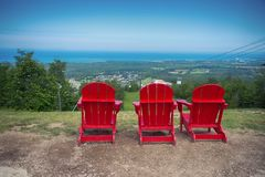 Muskoka chairs at Blue Mountain resort and village in Collingwoo. View of 3 red muskoka chairs at Blue Mountain resort and village during the summer in Stock Photography
