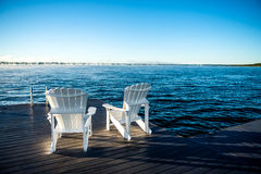 Muskoka Chairs on a dock with sun rising and mist Royalty Free Stock Images