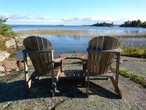 Muskoka chairs. At the lake Royalty Free Stock Photos