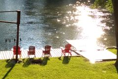 Muskoka chairs on the lake stock photo