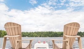 Muskoka chairs overlooking the lake with a bowl of cherries and a glass of champagne in between. stock image