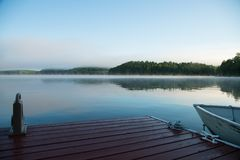 Muskoka dock and boat on a misty morning lake stock images