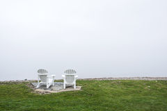 Muskoka-Stühle auf dem See konfrontieren mit weißem Himmel Stockfotos