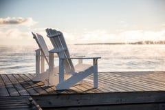 Muskoka-Stühle auf einem Dock mit dem Sonnensteigen und -nebel Stockbild