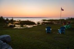 Muskoka stolar på en gräsmatta bredvid en sjö med en kanadensisk flagga i bakgrunden på solnedgången royaltyfria bilder