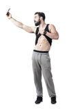 Muskulös abs för passformmanvisningen tränga sig in, medan ta selfie med den smarta telefonen Royaltyfria Foton