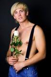 Muskulös härlig grabb med en ros i hans hand Arkivbild