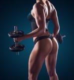 Muskulös idrotts- kvinna som utarbetar med vikter Royaltyfria Foton