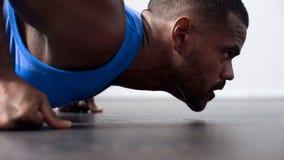 Muskulös idrottsman nen som värmer upp i idrottshallen som gör push-UPS för strid, karriär arkivbilder