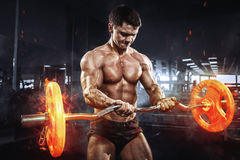 Muskulös idrottsman nenkroppsbyggare med brinnande skivstångbegrepp i idrottshall royaltyfri bild