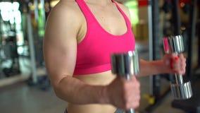 Muskulös idrottsman nenkvinna i en rosa överkant som utarbetar i idrottshalllyftande vikterna Konditionflicka som övar i idrottsh stock video