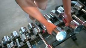 Muskulös idrottsman nenkvinna i idrottshalllyftande vikterna Konditionflickan tar en hantel Begreppet av sporten, skönhet, kondit arkivfilmer