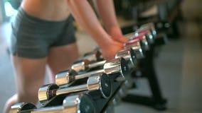 Muskulös idrottsman nenkvinna i idrottshalllyftande vikterna Konditionflickan tar en hantel Begreppet av sporten, skönhet, kondit lager videofilmer