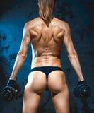 Muskulös konditionkvinna, sund livsstil, färdig kroppsbyggare för kors, idrotts- kropp för ` s, slut upp av barn med barben arkivbild