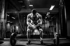 Muskulös konditionman som förbereder till deadlift en skivstång över hans huvud i modern konditionmitt Funktionell utbildning Arkivbild