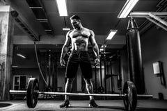 Muskulös konditionman som förbereder till deadlift en skivstång över hans huvud i modern konditionmitt Funktionell utbildning Arkivfoto
