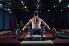Muskulös konditionman som förbereder till deadlift en skivstång över hans huvud i modern konditionmitt Funktionell utbildning bro Royaltyfri Bild