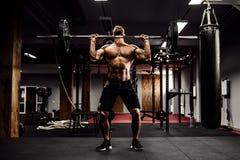 Muskulös konditionman som gör deadlift en skivstång över hans huvud i modern konditionmitt Funktionell utbildning Arkivbilder