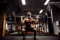Muskulös konditionman som gör deadlift en skivstång över hans huvud i modern konditionmitt Funktionell utbildning Arkivbild