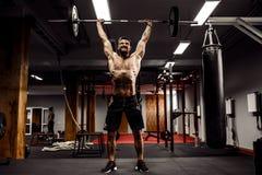 Muskulös konditionman som gör deadlift en skivstång över hans huvud i modern konditionmitt Funktionell utbildning Royaltyfri Bild