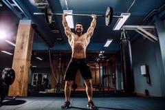Muskulös konditionman som gör deadlift en skivstång över hans huvud i modern konditionmitt Funktionell utbildning Arkivfoto