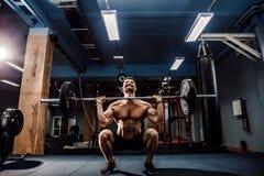 Muskulös konditionman som gör deadlift en skivstång i modern konditionmitt Funktionell utbildning Arkivbilder