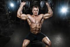 Muskulös kroppsbyggare för idrottsman nen i idrottshallutbildningen med hantlar arkivfoto