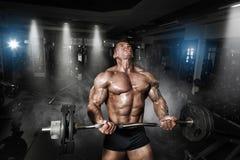 Muskulös kroppsbyggare för idrottsman nen i idrottshallutbildningen med stången arkivbilder