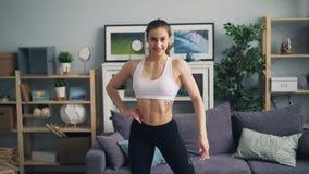 Muskulös kroppsbyggare för ung dam som ser kameran som ler den flyttande färdiga starka kroppen arkivfilmer
