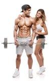 Muskulös kroppsbyggare med kvinnan som gör övningar med hantlar fotografering för bildbyråer