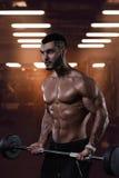 Muskulös kroppsbyggare som utarbetar i idrottshall royaltyfria bilder