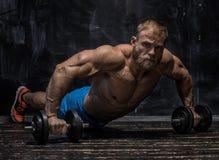 Muskulös kroppsbyggaregrabb över mörk bakgrund arkivbild