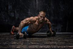 Muskulös kroppsbyggaregrabb över mörk bakgrund arkivbilder