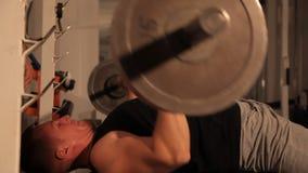 Muskulös kroppsbyggaregrabb som gör övningar lyfter stången lager videofilmer