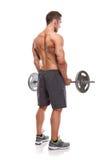 Muskulös kroppsbyggaregrabb som gör övningar med den stora hanteln över Arkivfoto