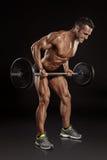 Muskulös kroppsbyggaregrabb som gör övningar med den stora hanteln Royaltyfria Foton