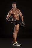 Muskulös kroppsbyggaregrabb som gör övningar med hantlar Arkivfoton