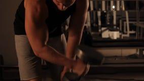 Muskulös kroppsbyggaregrabb som gör övningar med hantlar i idrottshall stock video